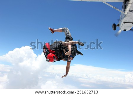 Two skydivers diving out of an airplane