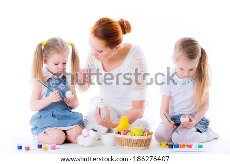 Two small cute sisters with beautiful mother paint Easter eggs