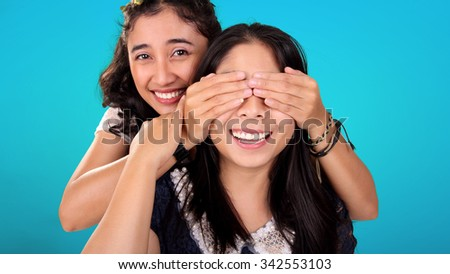 Two smiling Asian female friends play guess who game. One girl covering her friend's eyes from behind, over blue background