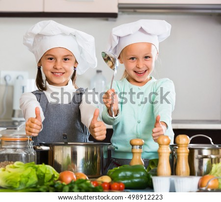 Two smiling cheerful  girls cooking vegetable soup at home kitchen
