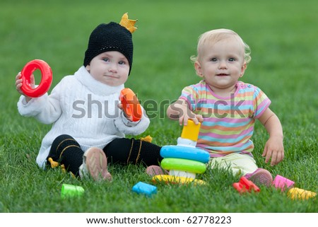 Two smiling little girls are playing with bright toys on the green grass