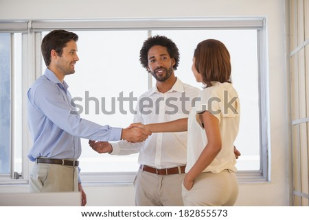 Two smiling young business people shaking hands besides colleague at the office