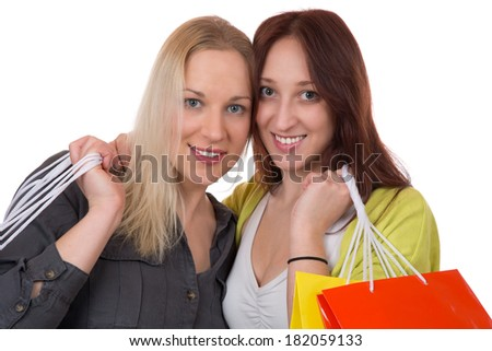 Two smiling young friends with shopping bags having fun while shopping, isolated on a white background