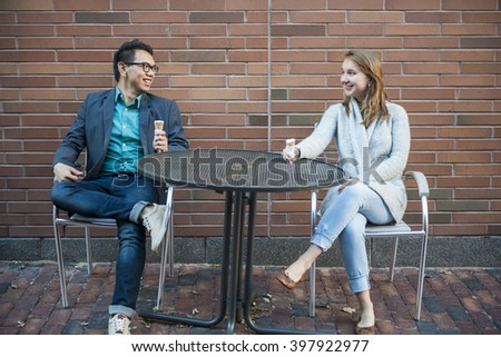 Two smiling young people with ice cream sitting at outdoor cafe table near brick wall having conversation