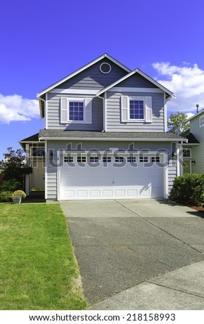 Two story house with small entrance porch and garage with driveway