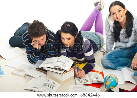 Two students reading a book while their colleague smiling for camera and together doing homework