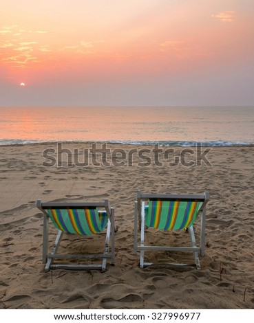 Two sun beach chairs on shore at sunrise in Thailand