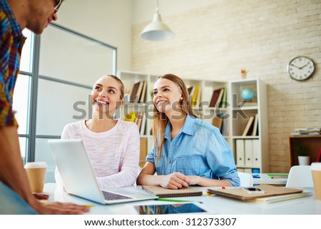Two teenage girls looking at their groupmate during conversation in college