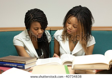Two teenage girls sitting with books in the library