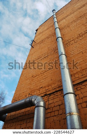 two ventilation pipes on a brick yellow wall