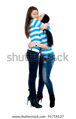 Two vigorous girls in striped vests look against each other and smile. Isolated on white.