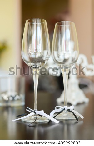 two wedding glasses with ribbons on table