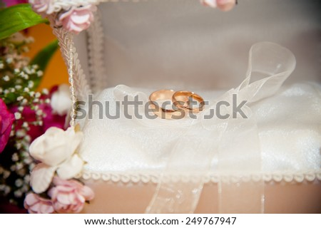 two wedding rings lie in the trunk for rings next to a bouquet of the bride