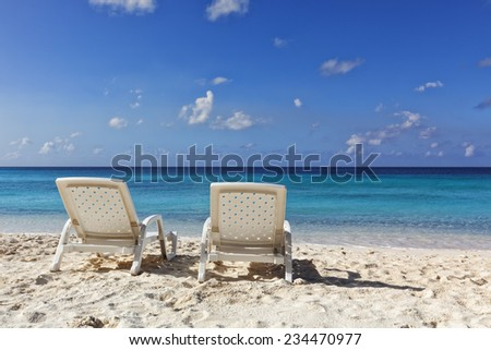 Two white deckchairs at tropical beach of Curacao