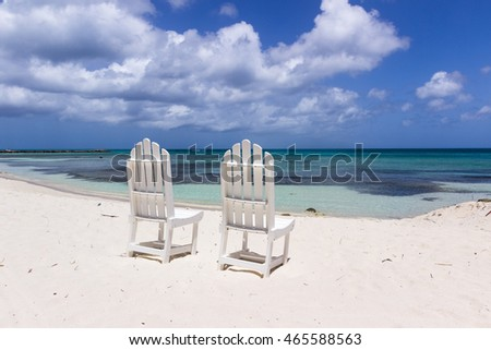 two white restaurant chairs on caribbean coast