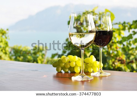 Two wineglasses and grapes against Geneva lake. Lavaux region, Switzerland