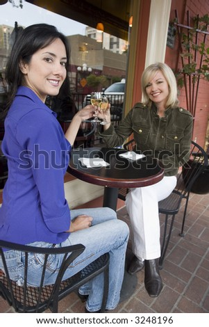 Two woman enjoying drinks outside