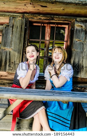 Two woman in traditional austrian clothes sitting by a wooden hut