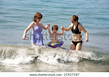 Two women and a baby playing in the ocean