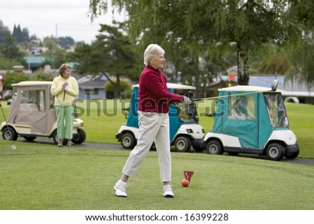Two women golfing, one is teeing off. Horizontally framed photo.