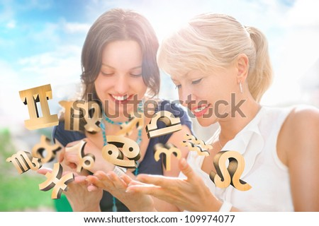 Two women mother and daughter sitting at summer park and having fun while discussing horoscope and different zodiac symbols appearing from their hands. Lots of copyspace