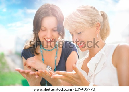 Two women mother and daughter sitting outdoors at summer park on beautiful bright sunny day and having fun