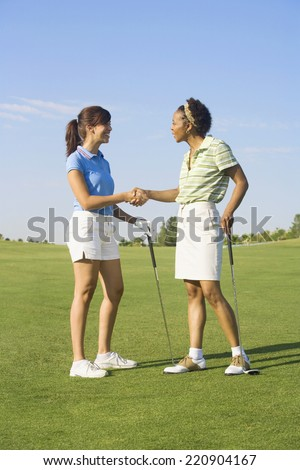 Two women shaking hands on golf course