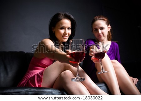 Two women toasting glasses of red wine (focus on the glass) at a party