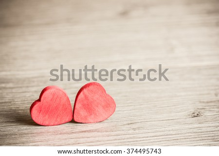 Two wooden hearts on wooden surface.