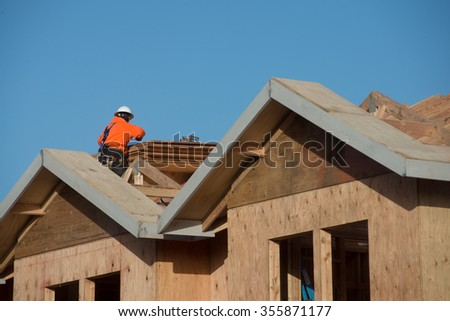 Two workers apply plywood to the top of an apartment under construction.