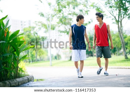 Two young athletic friends walking in the park and talking