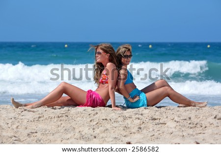 Two young attractive bikini clad women chilling on a sunny beach on holiday or vacation by the sea