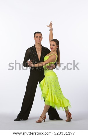 Two young ballroom dancers in studio taken against a high-key white background