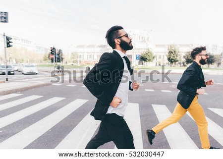 two young bearded blonde and black hair modern businessman, running in the city backlight, crossing pedestrian crossing - working, successful concept
