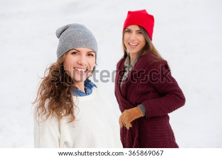 Two young beautiful sisters outdoor, in a cold winter day, looking playful, enjoying the snow.