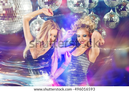 Two young beautiful women dancing at night disco club