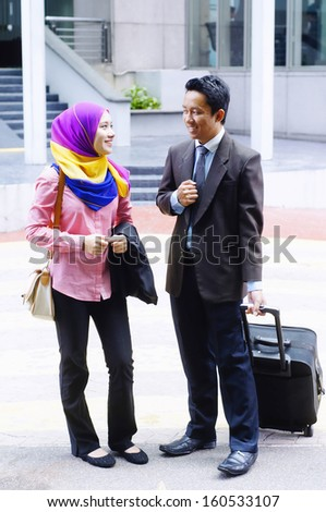 Two young business executive discussing while walking