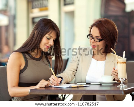 Two young businesswoman discussing in a cafe