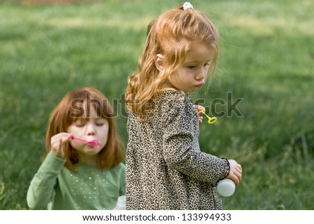 Two young Caucasian girls blowing bubbles