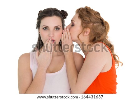 Two young female friends gossiping over white background
