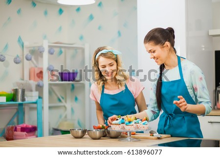 two young girls decorating cup cakes with fruit