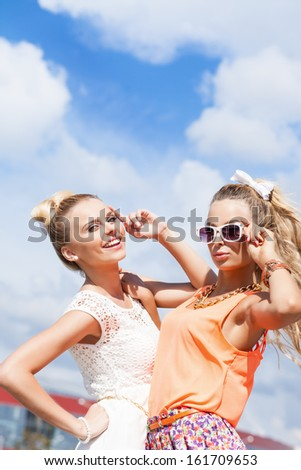 two young girls in summer outfit pose for the camera against the blue sky