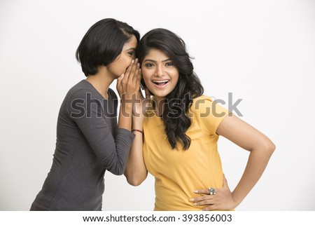 two young Indian women gossiping on white background.