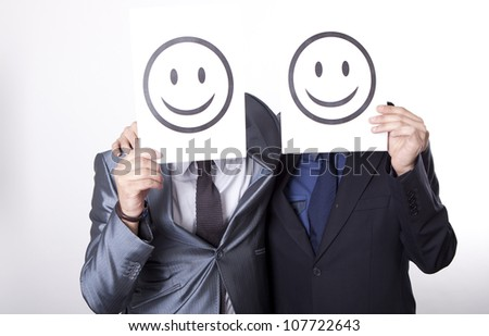 Two young men holding smiley faces.