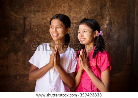 Two young Myanmar girls in a praying gesture.