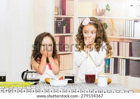 Two young preschooler girls covering their mouths refusing to eat their meal