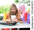 Two young pretty Asian muslim business woman in head scarf with book laptop - stock photo