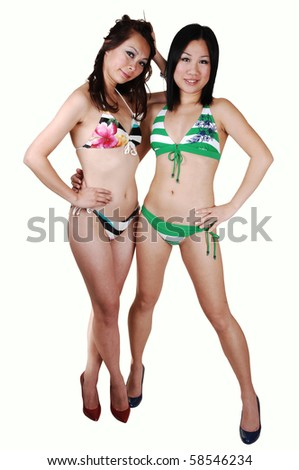 Two young pretty woman in colorful bikinis with long brunet and black hair in high heels for white background.