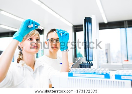Two young researchers carrying out experiments in a lab (shallow DOF; color toned image)