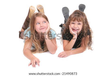 two young smiling female children friends laying down together over white